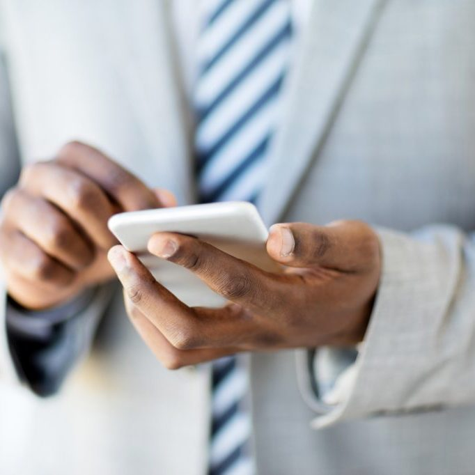 closeup african man using cell phone in office